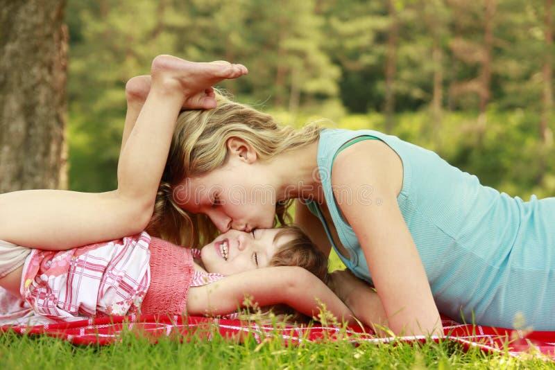 Potomstwo matka i jej mała córka bawić się na trawie fotografia stock