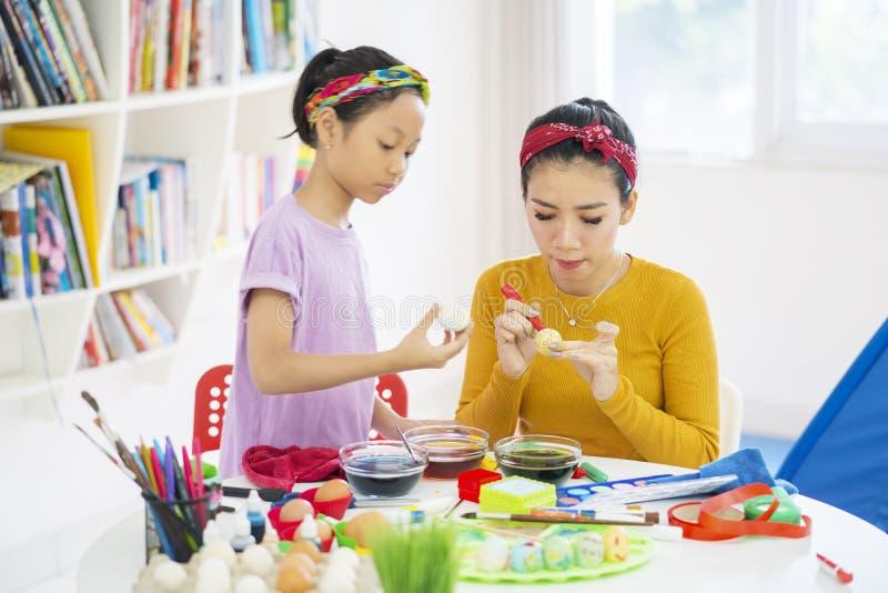 Potomstwo matka uczy jej córki farb jajka obraz stock