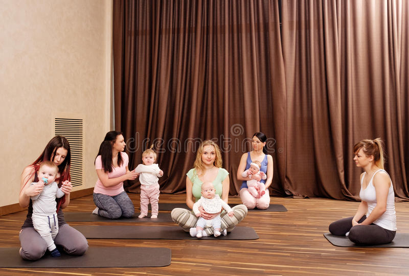 Potomstwo matki i ich dzieci robi joga ćwiczeniom na dywanikach przy sprawności fizycznej studiiem obraz stock