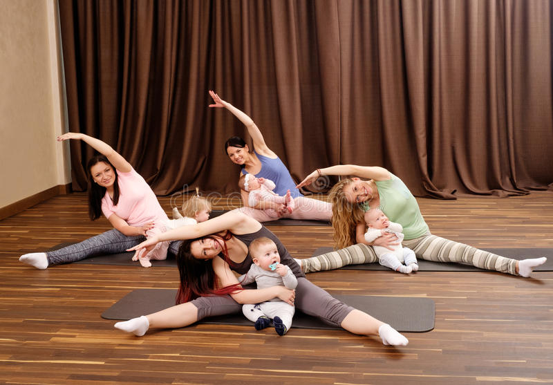 Potomstwo matki i ich dzieci robi joga ćwiczeniom na dywanikach przy sprawności fizycznej studiiem fotografia stock