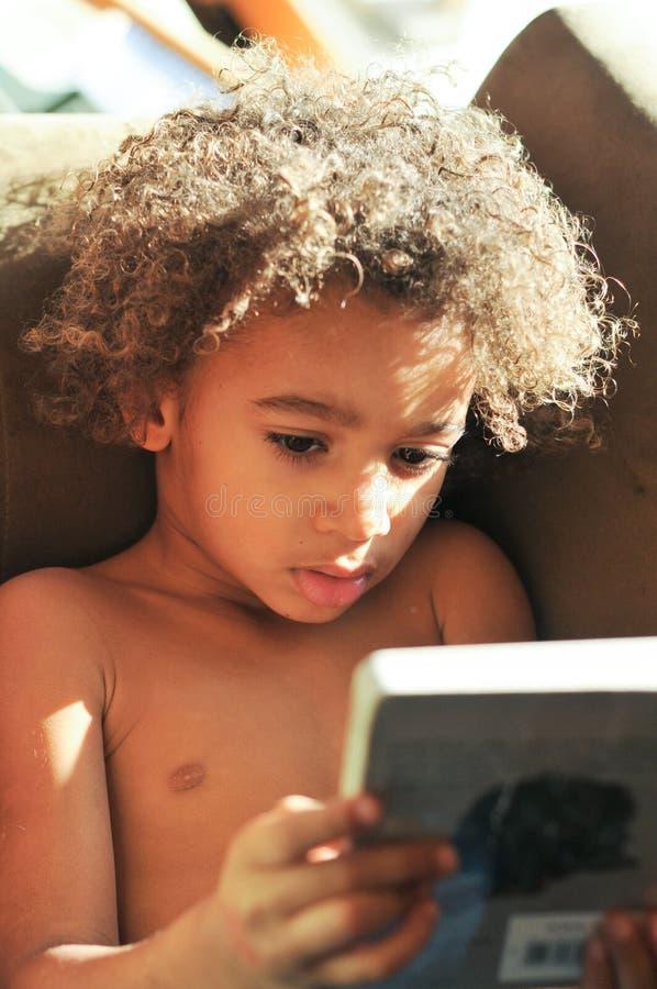 Potomstwo mieszająca biegowa chłopiec z kędzierzawego włosy czytaniem obraz stock
