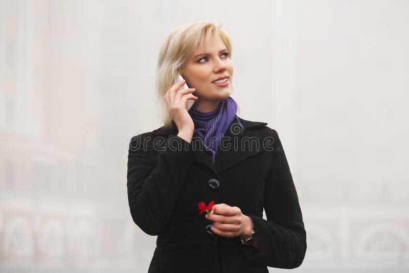 Potomstwo mody kobieta opowiada na telefonu komórkowego odprowadzeniu w miasto ulicie obraz stock