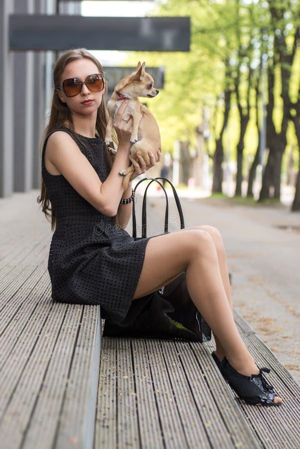 Potomstwo mody kobieta, siedzi z jej psem na schodkach zdjęcia stock