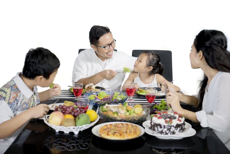 Potomstwo ojciec karmi jego córki na studiu obrazy stock