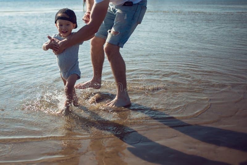 Potomstwo ojciec uczy dziecka spacer mężczyzna z dzieckiem bawić się morzem zdjęcie stock