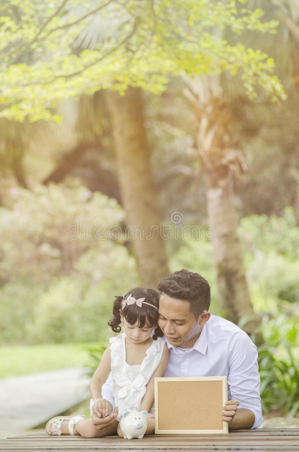 Potomstwo ojciec uczy jego córki oszczędzania pieniądze zdjęcia stock