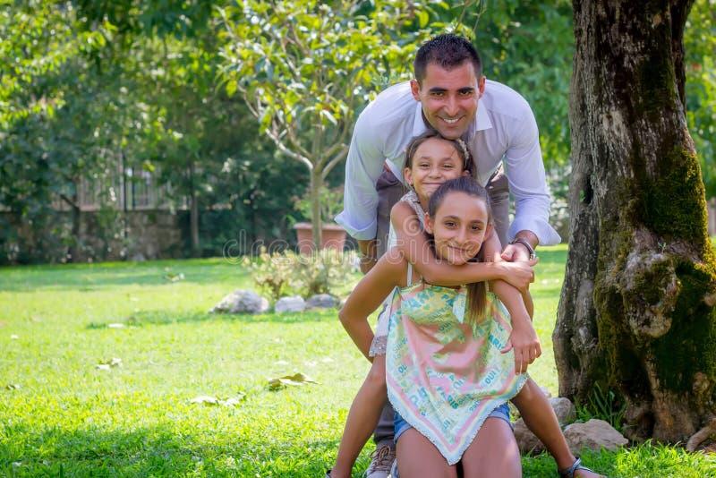 Potomstwo ojciec z Dwa córkami w parku w lecie obraz stock