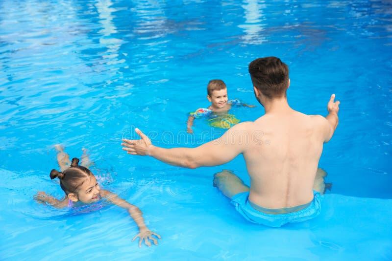 Potomstwo ojciec z małymi dziećmi w pływackim basenie obrazy royalty free