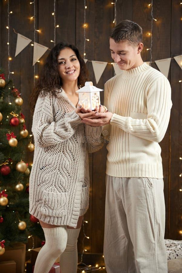Potomstwo para świętuje nowego roku Bożonarodzeniowe światła i dekoracja Ubierający w białym pulowerze Jedlinowy drzewo na ciemny zdjęcia stock