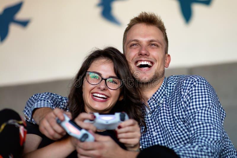 Potomstwo para bawić się wideo gry w domu obraz stock