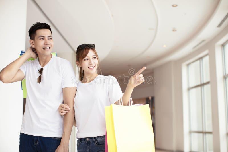 Potomstwo para chodzi w centrum handlowym z torba na zakupy fotografia royalty free