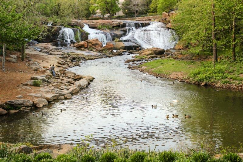 Potomstwo para cieszy się widok siklawy w Greenville spadków parku fotografia royalty free