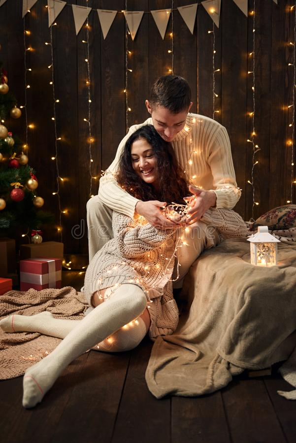 Potomstwo para jest w bożonarodzeniowych światłach i dekoracji ubierających w, białym, jedlinowym drzewie na ciemnym drewnianym t zdjęcie royalty free