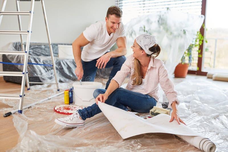 Potomstwo para ma zabawę przy wallpapering obraz royalty free
