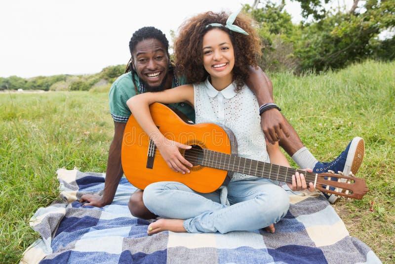 Potomstwo para na pyknicznej bawić się gitarze zdjęcie royalty free