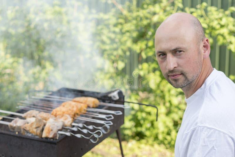 Potomstwo para robi grillowi w ich ogródzie Mężczyzna kulinarny mięso na grillu obraz stock