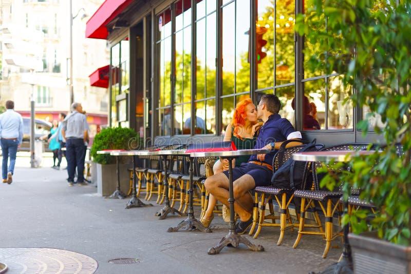 Potomstwo para siedzi w Paryjskiej kawiarni obrazy stock