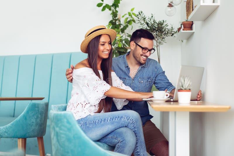 Potomstwo para używa laptop w kawiarni zdjęcie royalty free