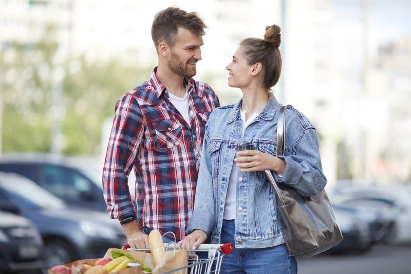 Potomstwo para z sklepami spożywczymi w parking zdjęcia stock