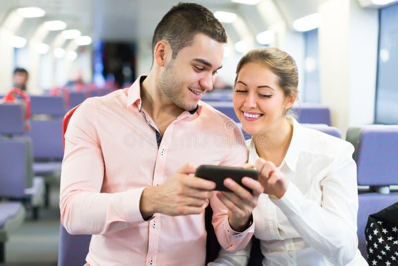 Potomstwo para z smartphones w pociągu fotografia royalty free
