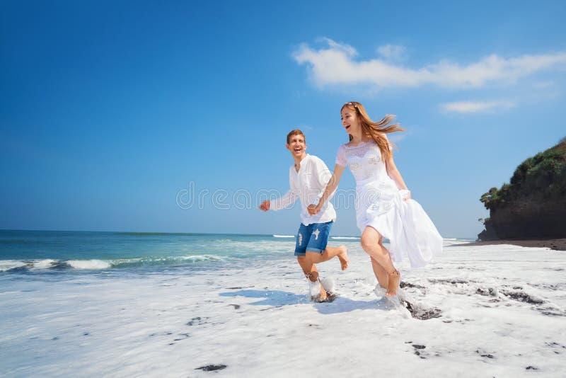 Potomstwo pary bieg czarną piasek plażą wzdłuż dennej kipieli obrazy stock