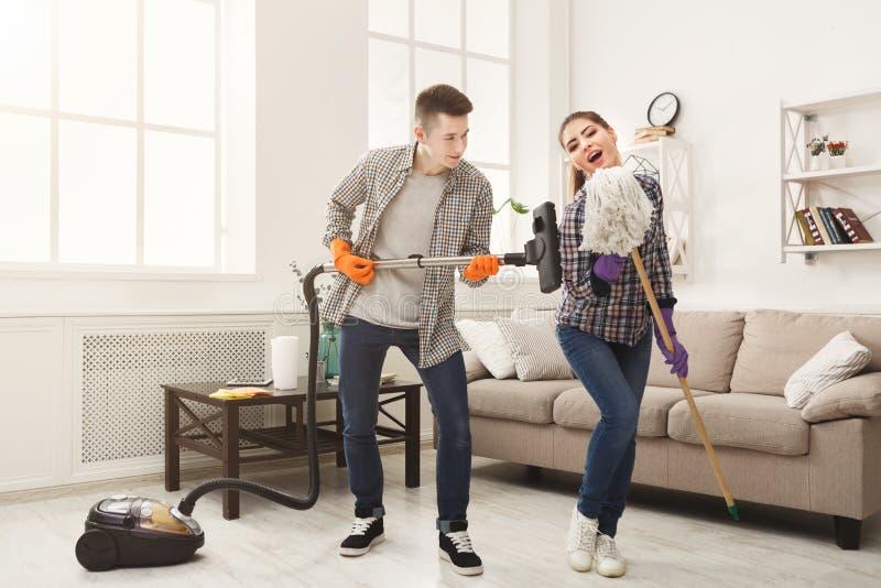 Potomstwo pary cleaning dom, mieć zabawę obraz stock