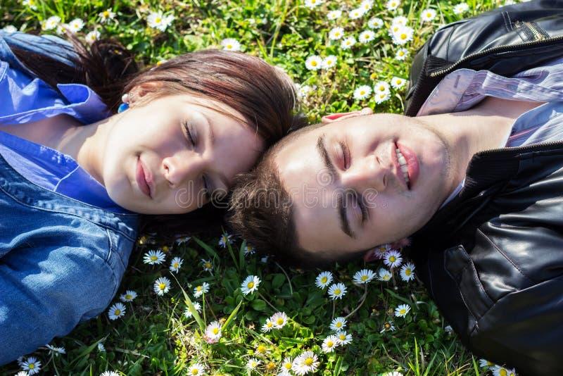 Potomstwo pary lying on the beach na trawie fotografia royalty free