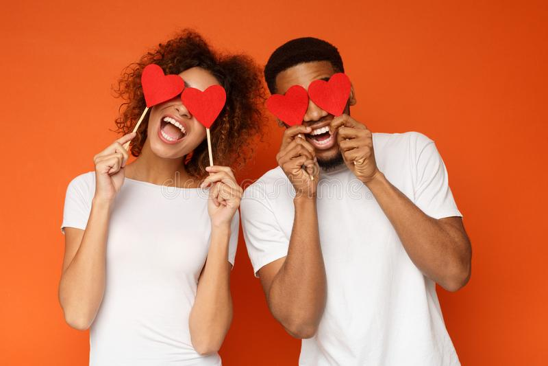 Potomstwo pary mienia miłości czerwoni serca nad oczami obraz stock