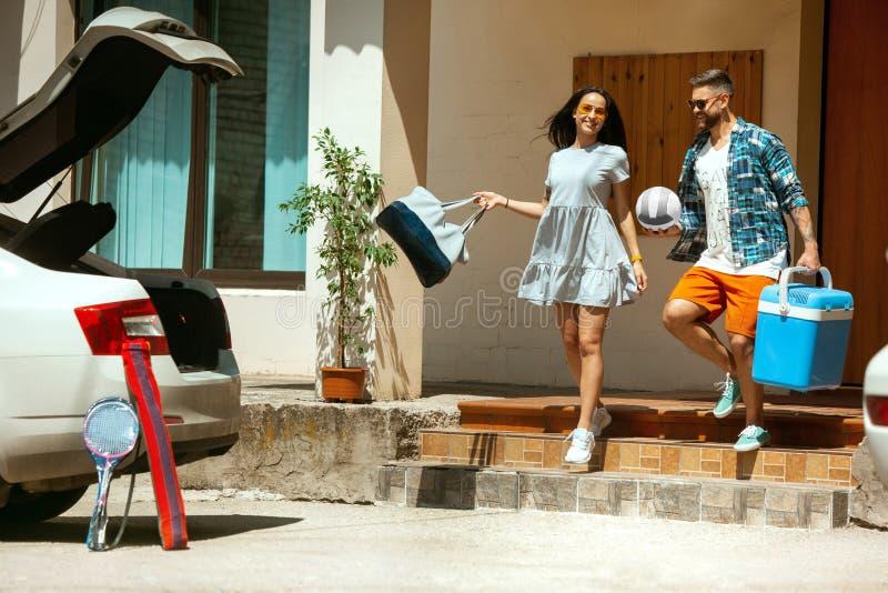 Potomstwo pary narządzanie dla urlopowej wycieczki na samochodzie w słonecznym dniu obrazy royalty free