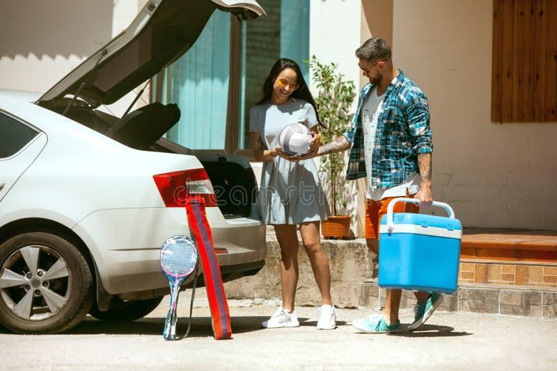 Potomstwo pary narządzanie dla urlopowej wycieczki na samochodzie w słonecznym dniu zdjęcie stock