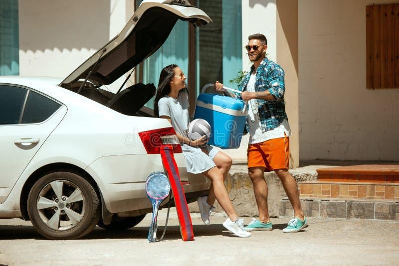 Potomstwo pary narządzanie dla urlopowej wycieczki na samochodzie w słonecznym dniu fotografia stock