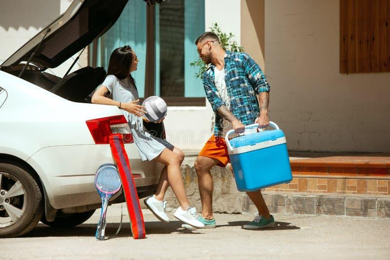 Potomstwo pary narządzanie dla urlopowej wycieczki na samochodzie w słonecznym dniu zdjęcia royalty free