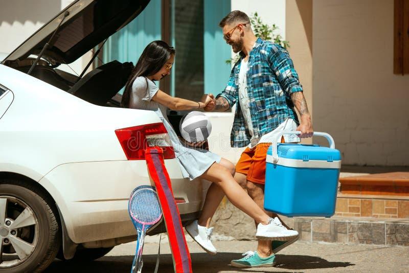 Potomstwo pary narządzanie dla urlopowej wycieczki na samochodzie w słonecznym dniu obraz royalty free