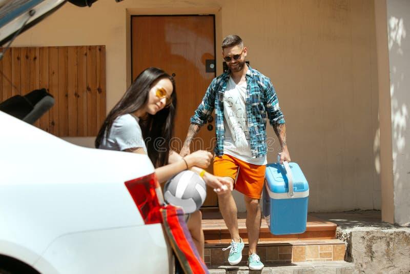 Potomstwo pary narządzanie dla urlopowej wycieczki na samochodzie w słonecznym dniu zdjęcie royalty free
