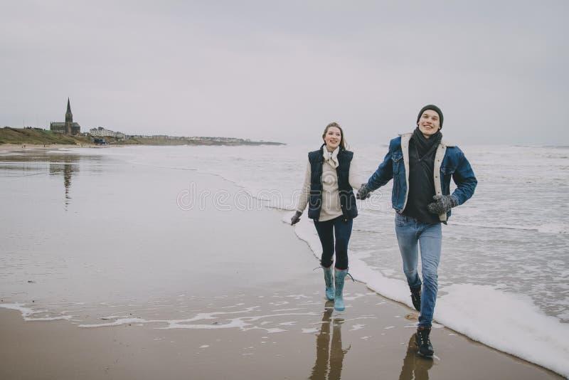 Potomstwo pary odprowadzenie Wzdłuż zimy plaży obrazy stock