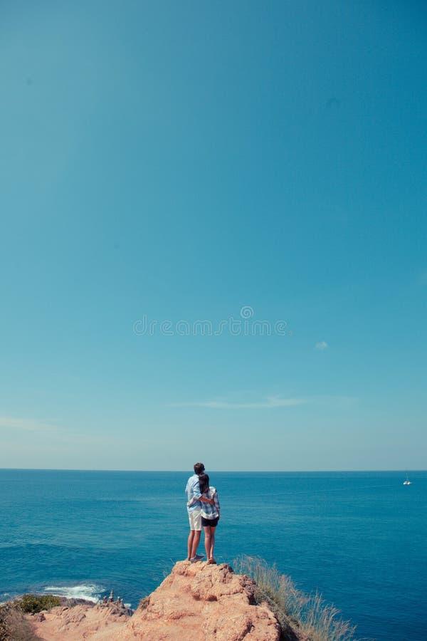 Potomstwo pary spojrzenie przy morzem fotografia stock