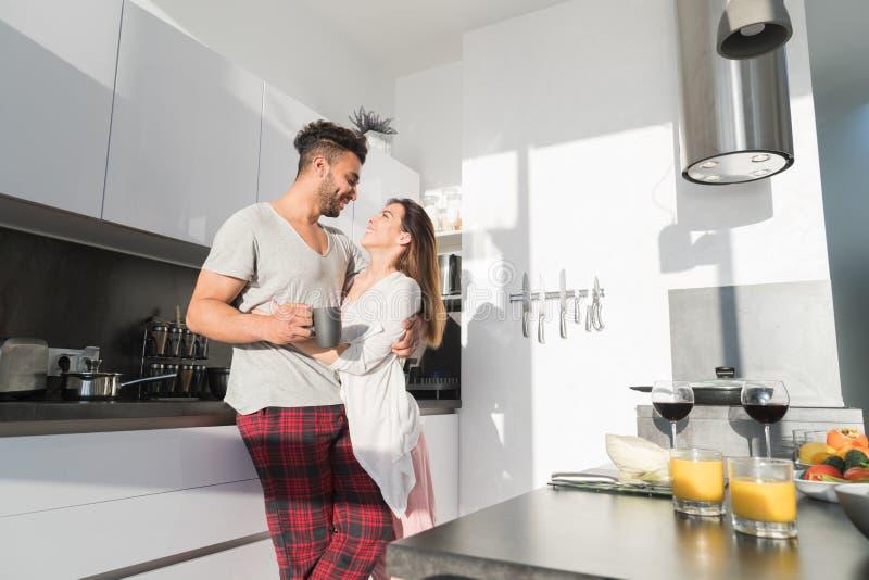 Potomstwo pary uścisk W kuchni, Latynoskim mężczyzna I azjata kobiecie, uściśnięcia ranku śniadanie obrazy royalty free