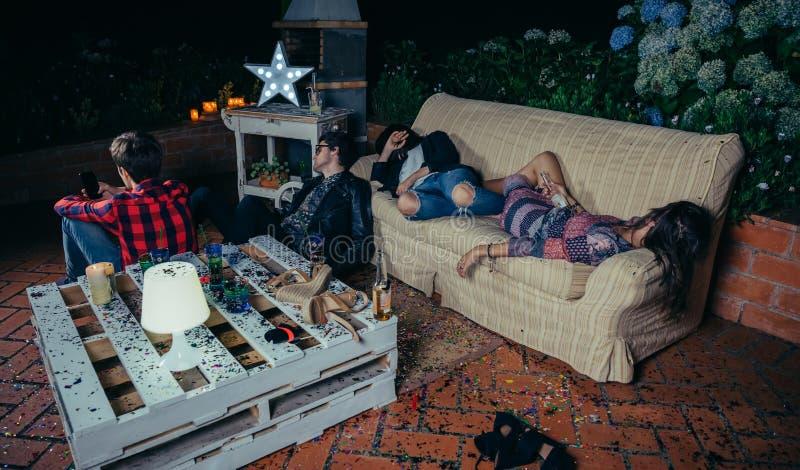 Potomstwo pijący przyjaciele śpi w kanapie po przyjęcia obrazy royalty free