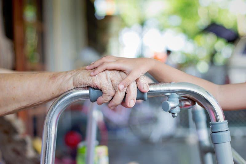 Potomstwo ręki dotyka starej kobiety ręka zdjęcie royalty free