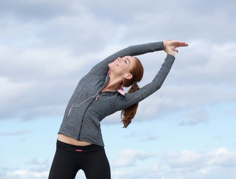 Potomstwo sportów kobieta ono uśmiecha się outdoors i rozciąga zdjęcia stock