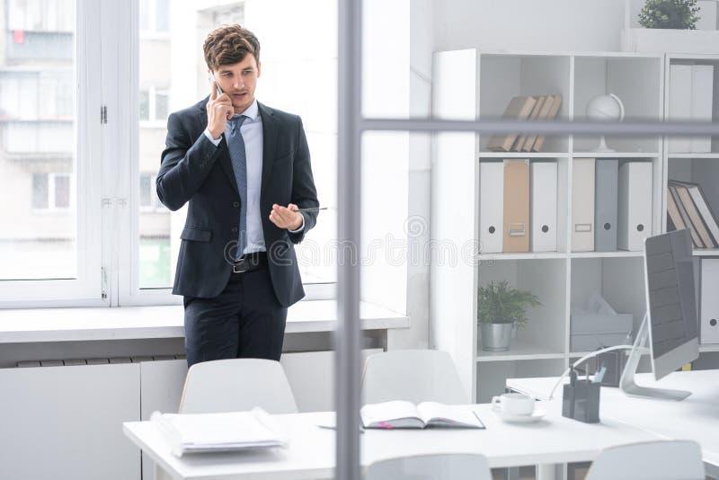 Potomstwo szefa mówienie telefonem obrazy stock