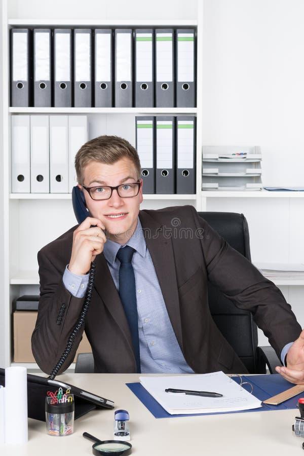 Potomstwo szokujący biznesmen dzwoni w biurze obraz stock