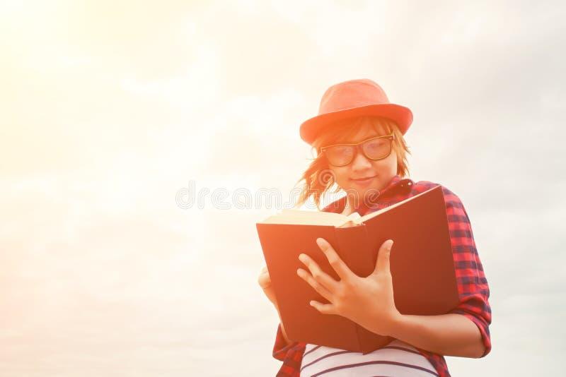 Potomstwo wykształcona kobieta stoi czytelniczą książkę obraz stock