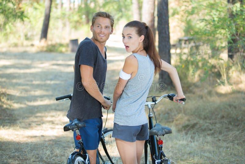 Potomstwo zaskakująca para z bicyklami w lesie fotografia stock