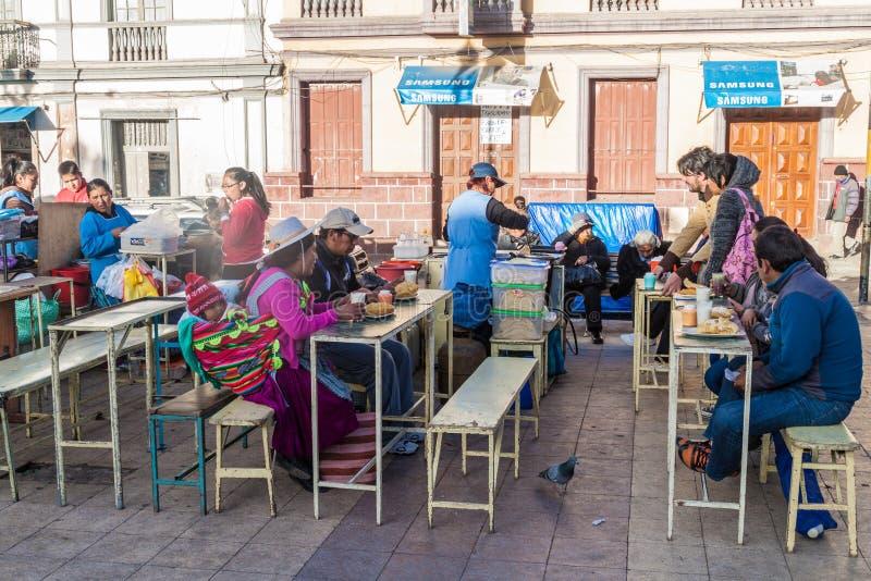 POTOSI, BOLIVIE - 19 AVRIL 2015 : Personnes locales mangeant sur un marché dans le Potos images stock