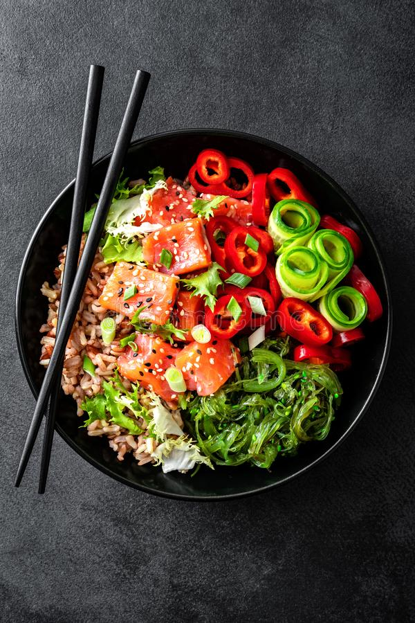 Potrącenie puchar brązów ryż, pstrąg, łosoś lub warzywa na ciemnym tle polędwicowi, Chuka gałęzatki sałatki, sezamowych i świeżyc obrazy royalty free
