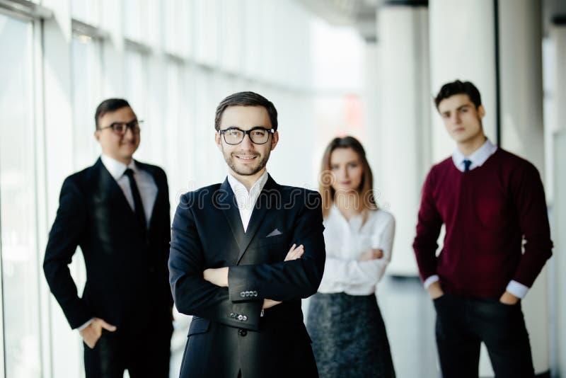 Potrait ενός επιχειρηματία που στέκεται μπροστά από την επιχειρησιακή ομάδα στην αίθουσα γραφείων στοκ εικόνες