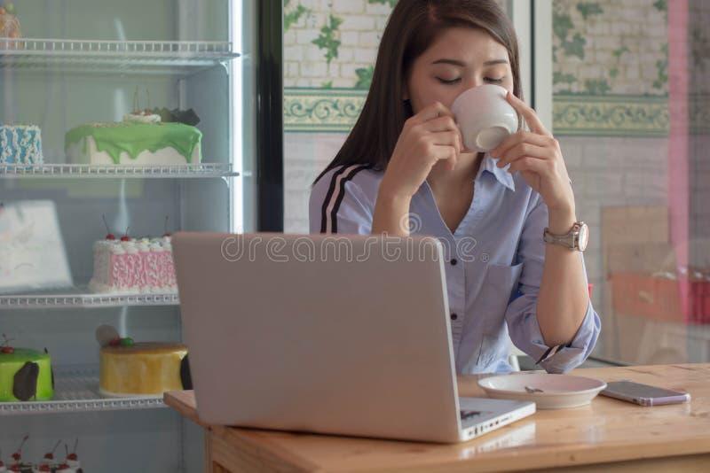 Potrait atrakcyjne azjatykcie kobiety pije fili?ank? przy tortowym sklepem kawa z laptopem i smartphone zdjęcia royalty free