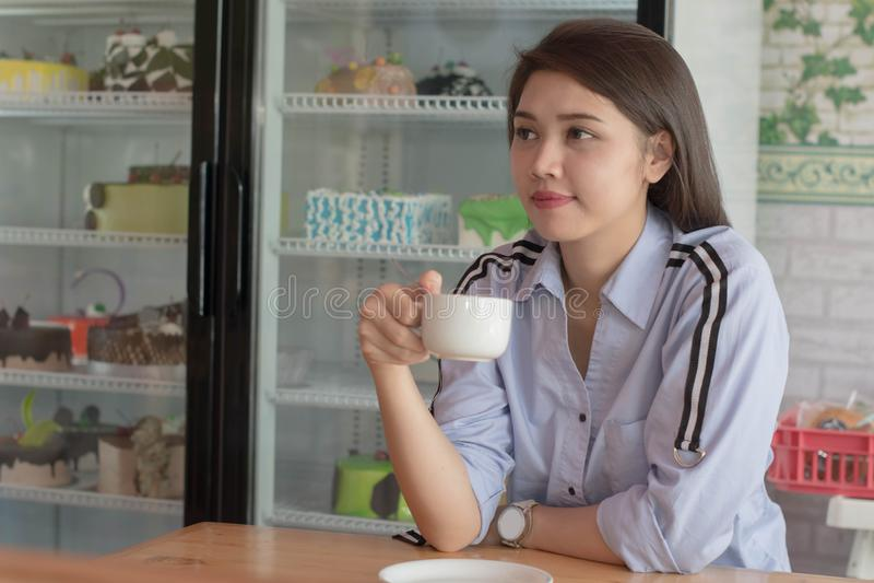 Potrait atrakcyjne azjatykcie kobiety pije fili?ank? przy tortowym sklepem kawa zdjęcie stock