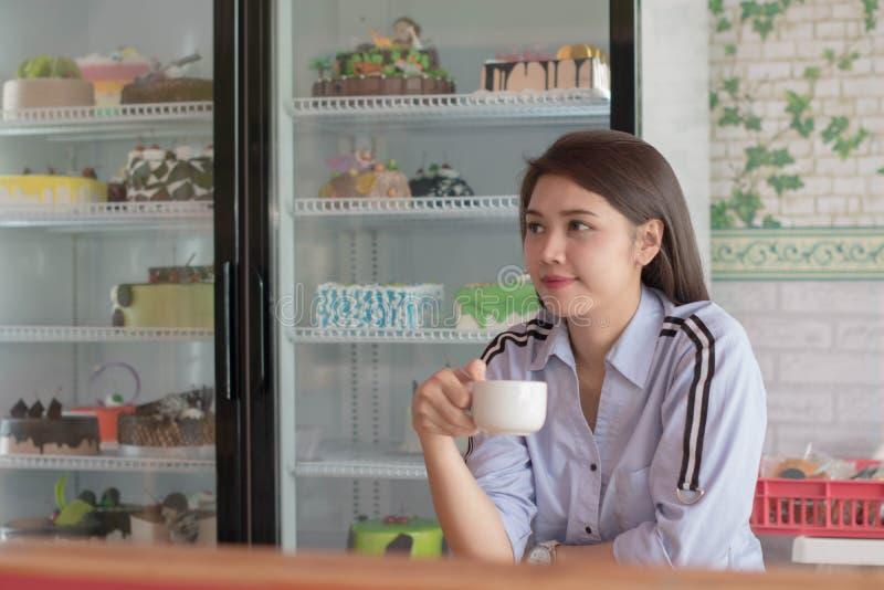 Potrait atrakcyjne azjatykcie kobiety pije fili?ank? przy tortowym sklepem kawa obrazy royalty free